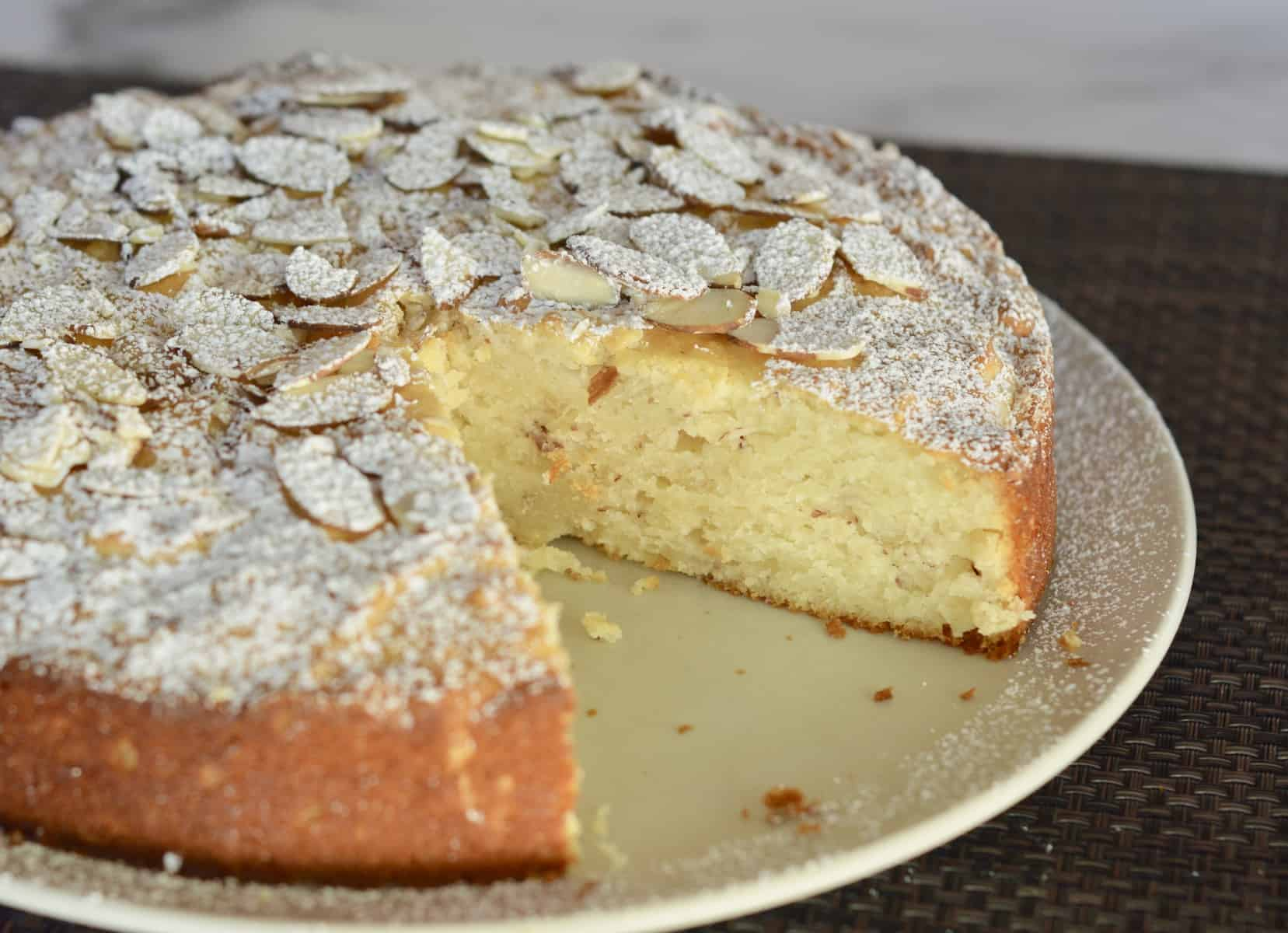 Almond dessert with slice almonds and powdered sugar on top.