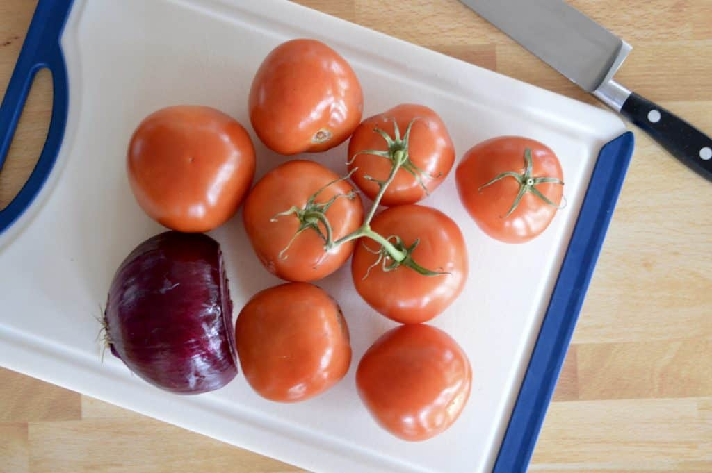 fresh tomatoes and red onion on a white cutting board.