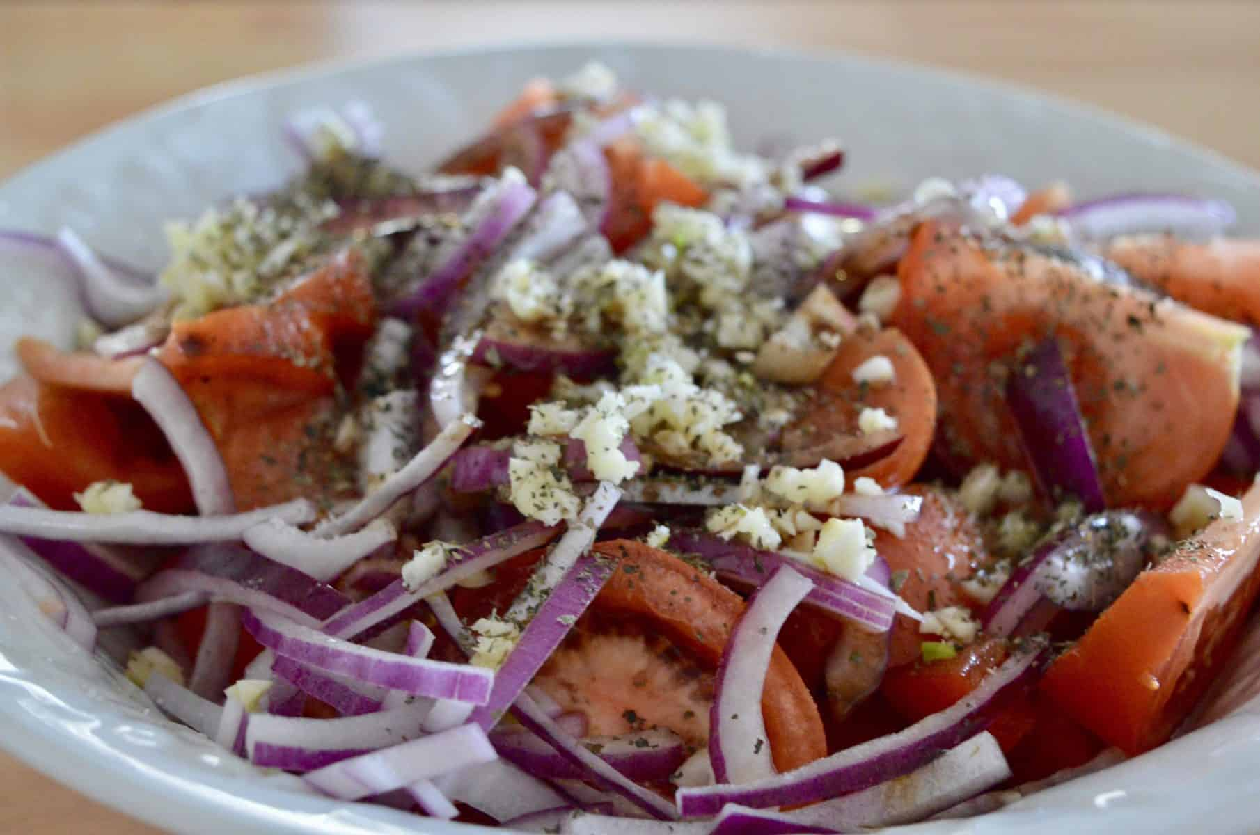 tomatoes, red onions, garlic, balsamic, olive oil, and oregano in a bowl.