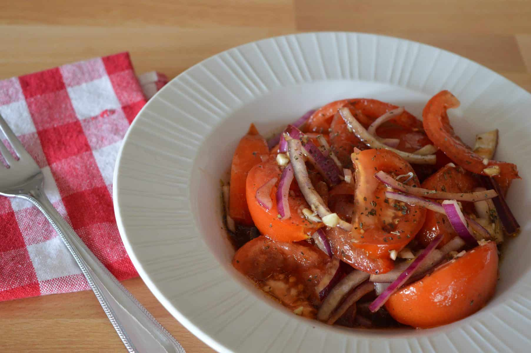 Italian Tomato Onion Salad in a white bowl with a red and white checker napkin next to it.