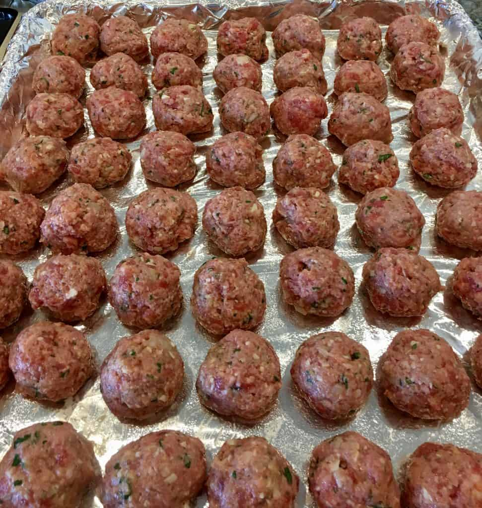 balls of meat rolled on a foil lined baking sheet.