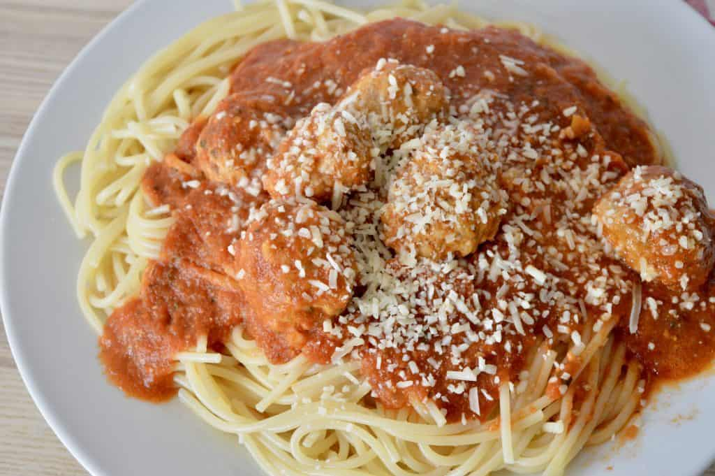 meatballs and spaghetti on a a white plate.