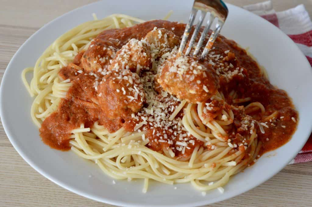 Italian Turkey Sausage Meatballs in marinara sauce over spaghetti in a white plate.
