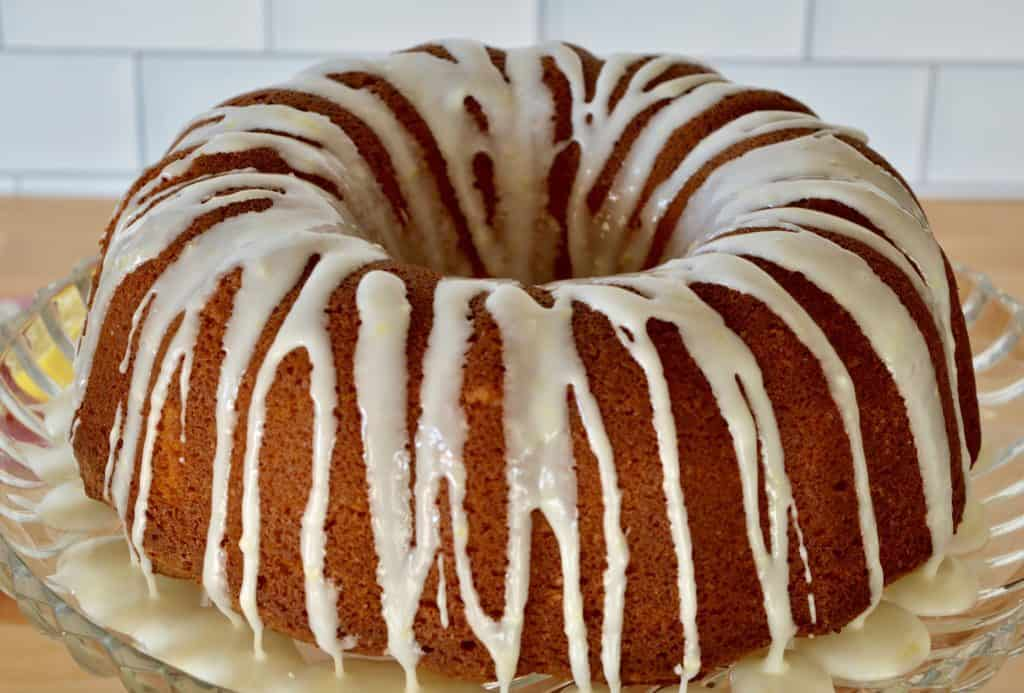 olive oil bundt cake on a glass pedestal with honey lemon drizzle.