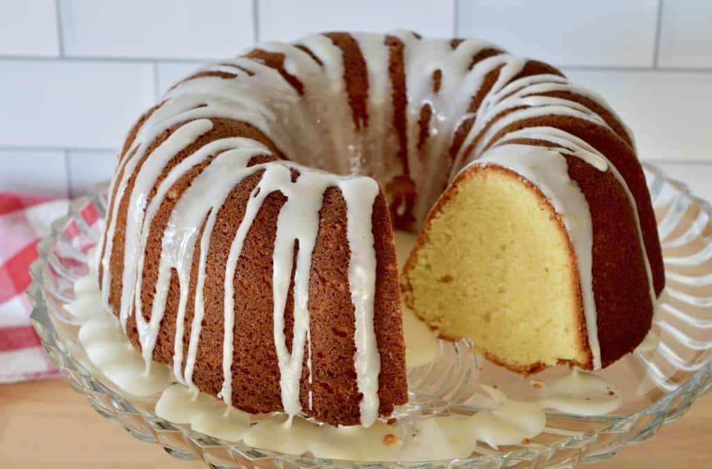 Lemon Olive Oil Bundt Cake with honey lemon glaze on a glass pedestal.