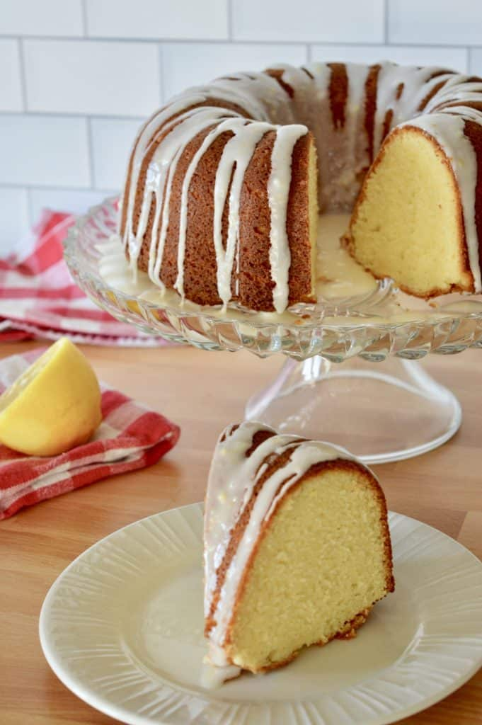olive oil yogurt bundt cake on a pedestal with a checkered napkin in the background.