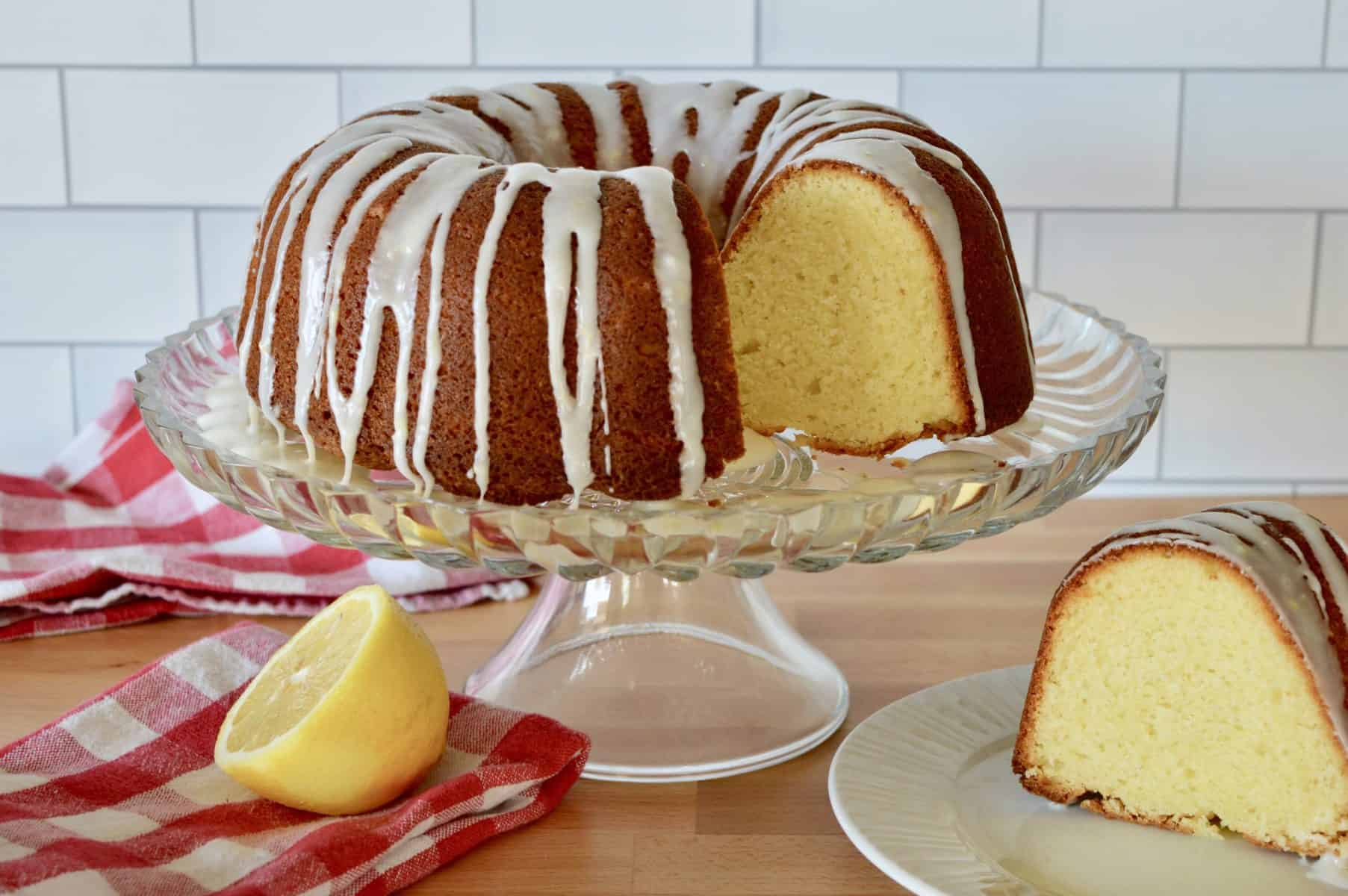 Olive Oil Bundt Cake on a pedestal with a slice of cake on a white plate and a half of a lemon.