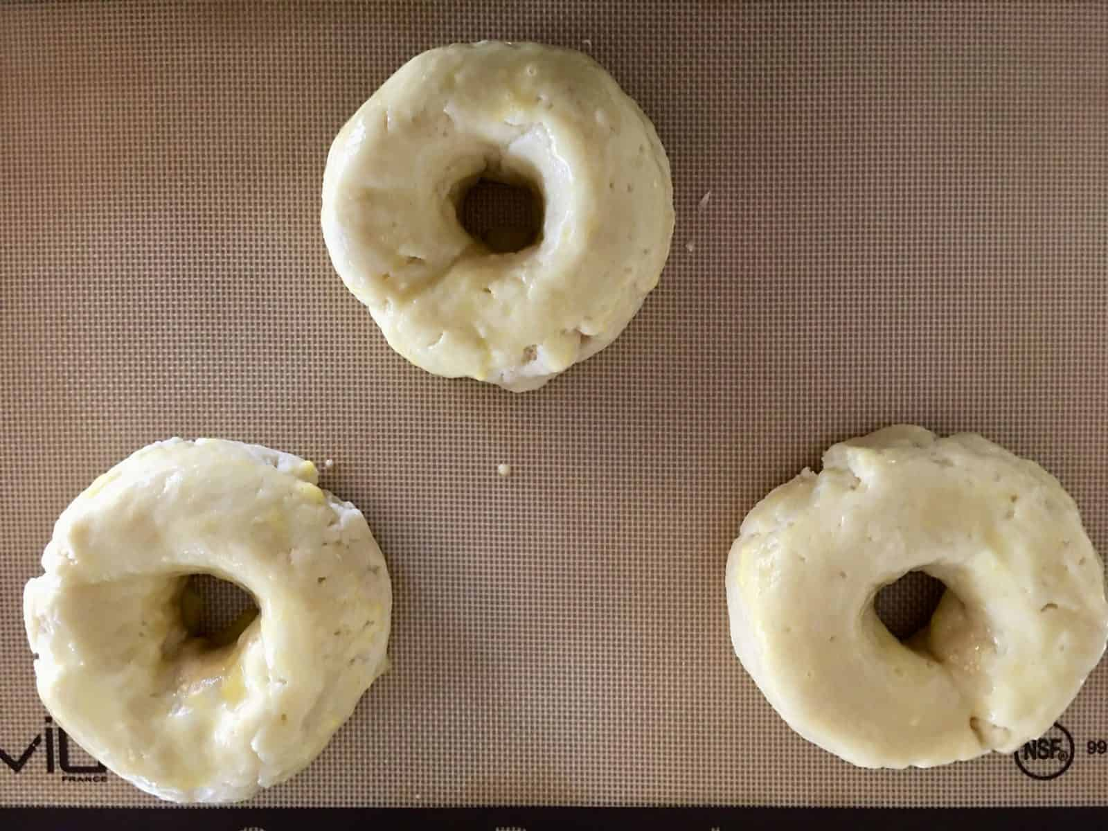 dough formed into donut shapes on a baking mat.