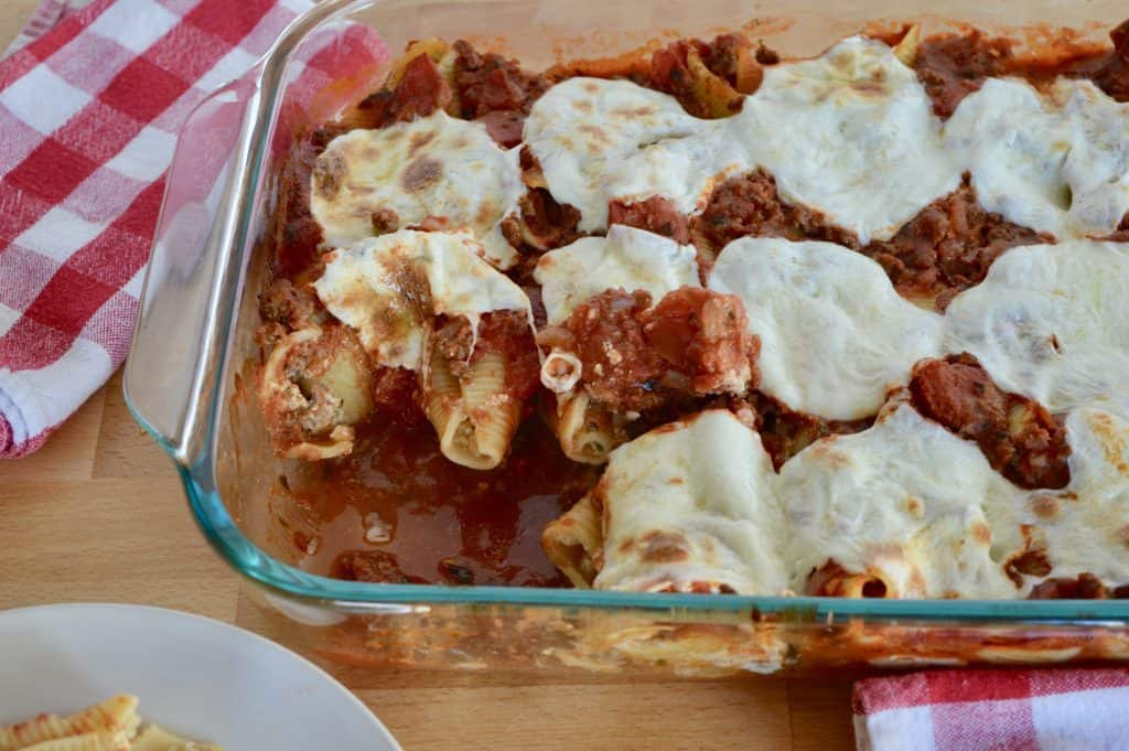 baked pasta in a glass baking dish with mozzarella cheese slices melted on top.