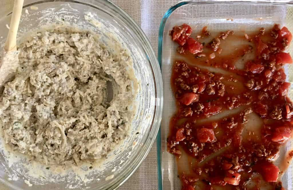 sauce on bottom of glass baking dish with a bowl of ricotta meat filling next to it.