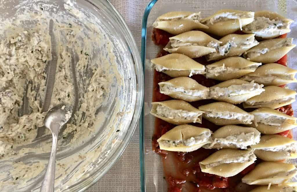 stuffed shells in baking dish with bowl of ricotta meat mixture next to it.
