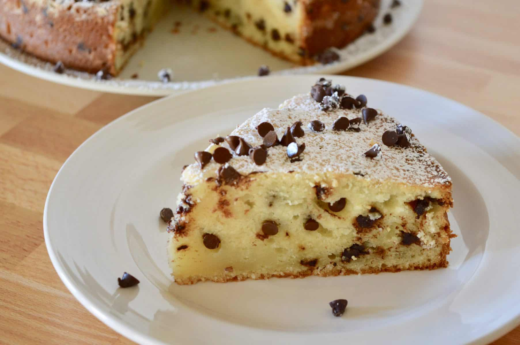 slice of chocolate chip ricotta cake on a white plate.