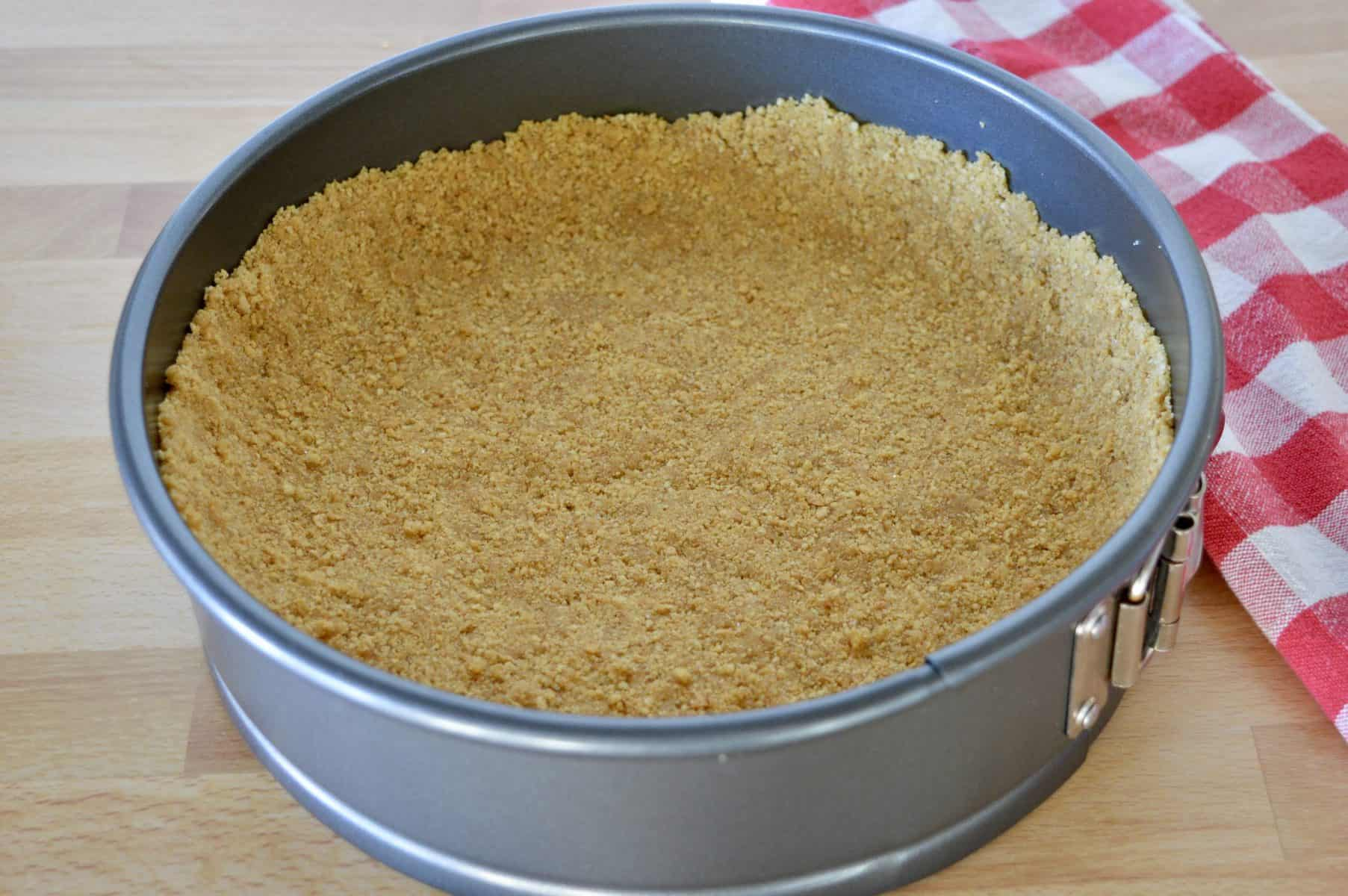 Graham cracker crumbs pressed into the bottom of a springform pan.