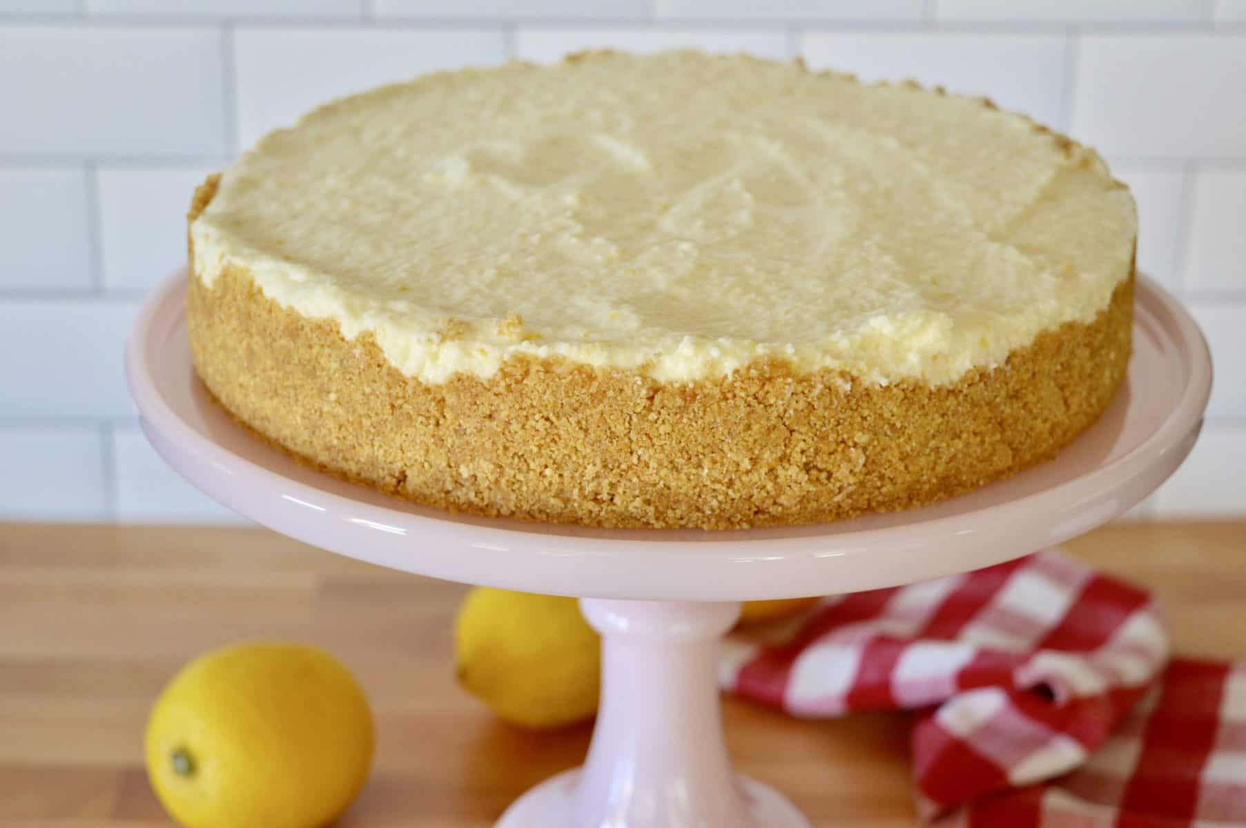 ungarnished no-bake lemon mascarpone cheesecake on a pink cake pedestal.