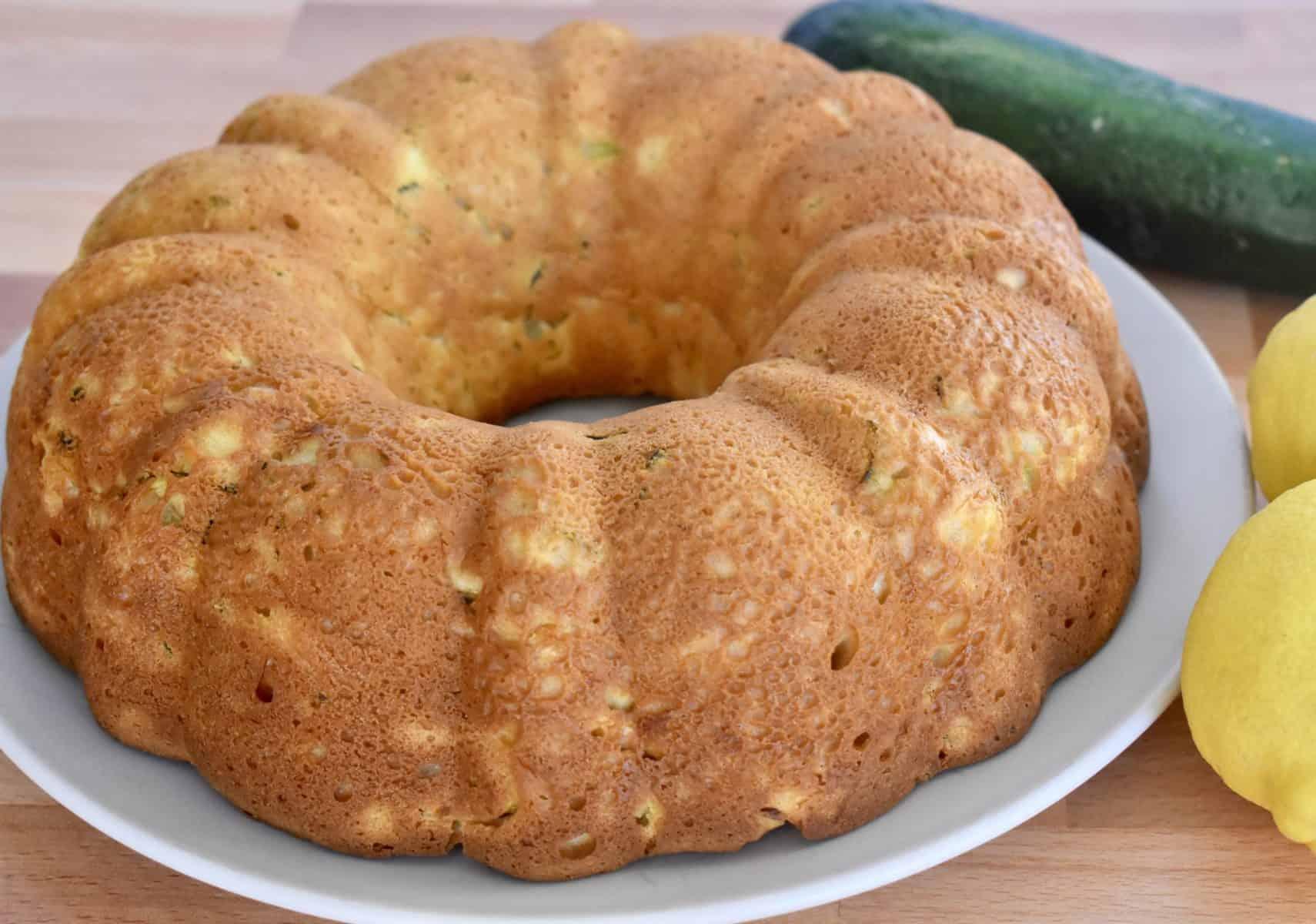 Zucchini Ricotta Cake on a plate with lemon and zucchini next to it.