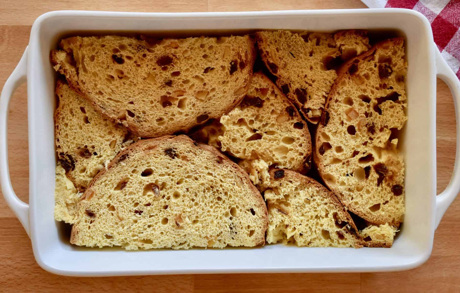 slices of panettone in a white baking dish.