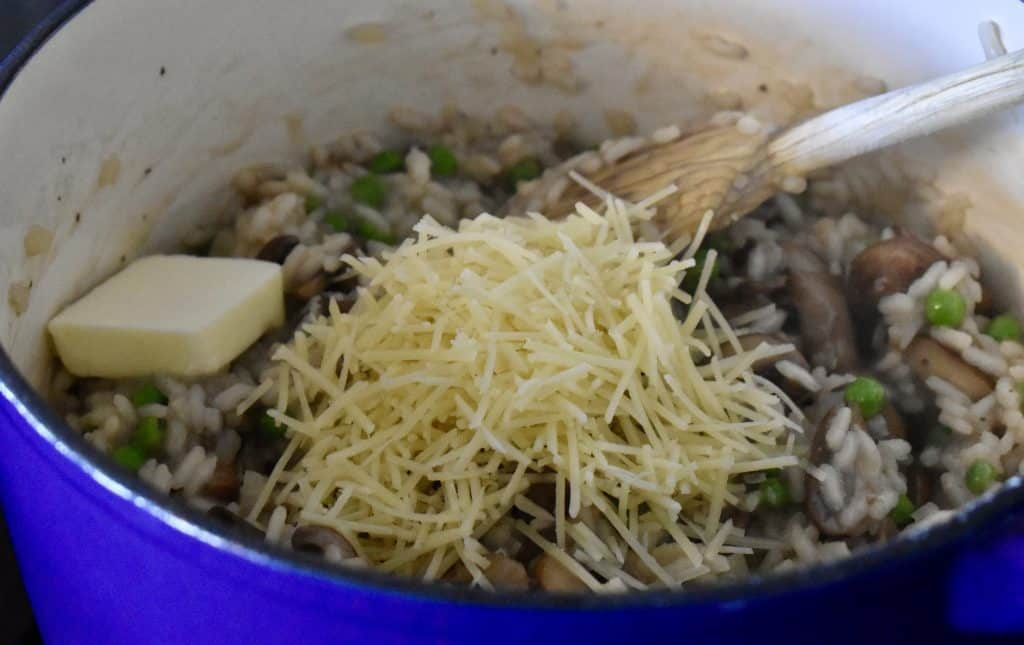 butter and parmesan cheese on the mushroom pea risotto in the pot.