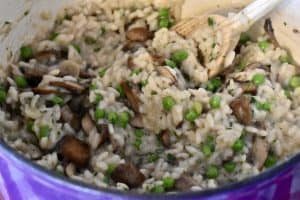 Finished Mushroom Pea Risotto in the cooking pot with a wooden spoon.