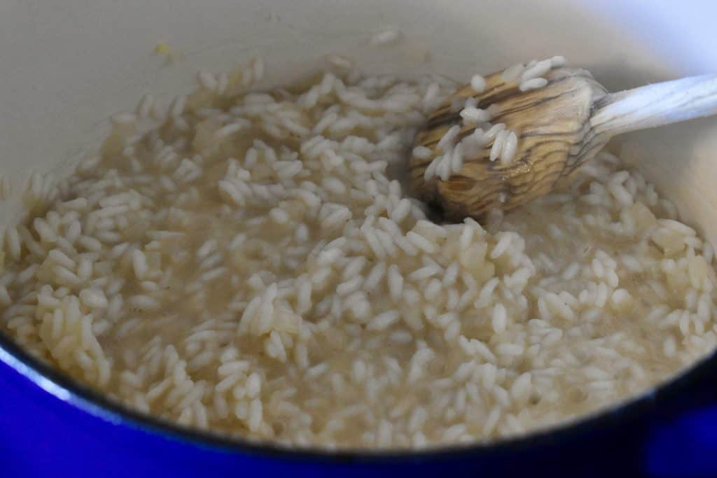 arborio rice almost completely cooked in a pot