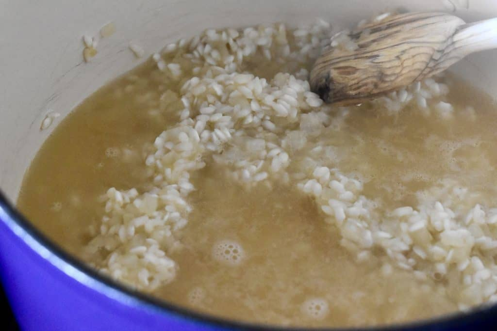 hot broth added to the arborio rice in a pot.