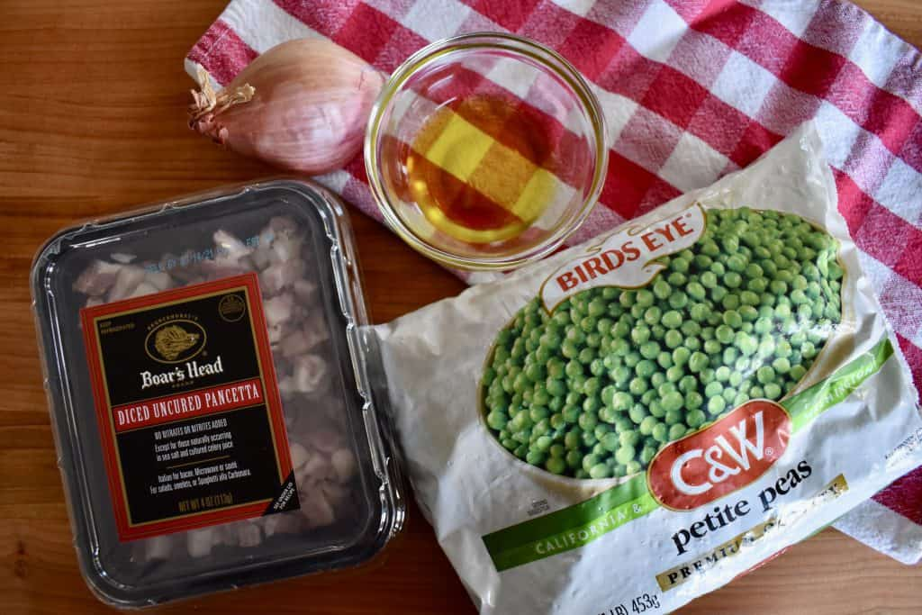 bag of frozen peas, diced pancetta, olive oil, and shallot on a checkered napkin.