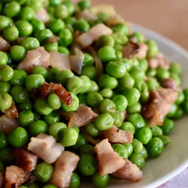 Peas and Pancetta piled high on a white plate.