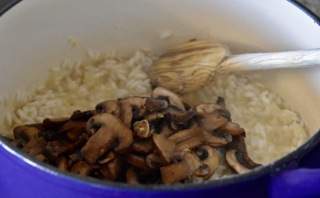 Mushrooms added to the pot of arborio rice.