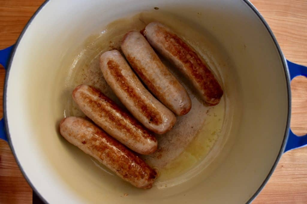 Sausages browned in a dutch oven skillet.