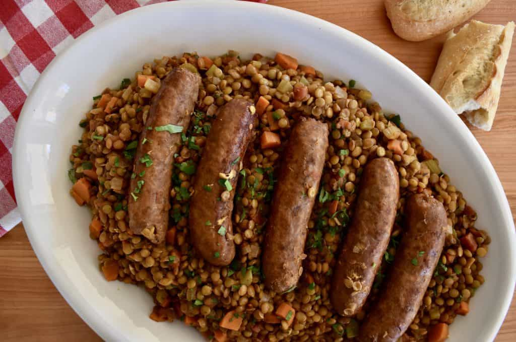 overhead photo of a platter of lentils with Italian sausage on top.