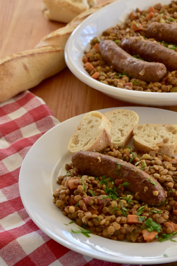Italian Sausage and Lentils on a white serving platter with bread.