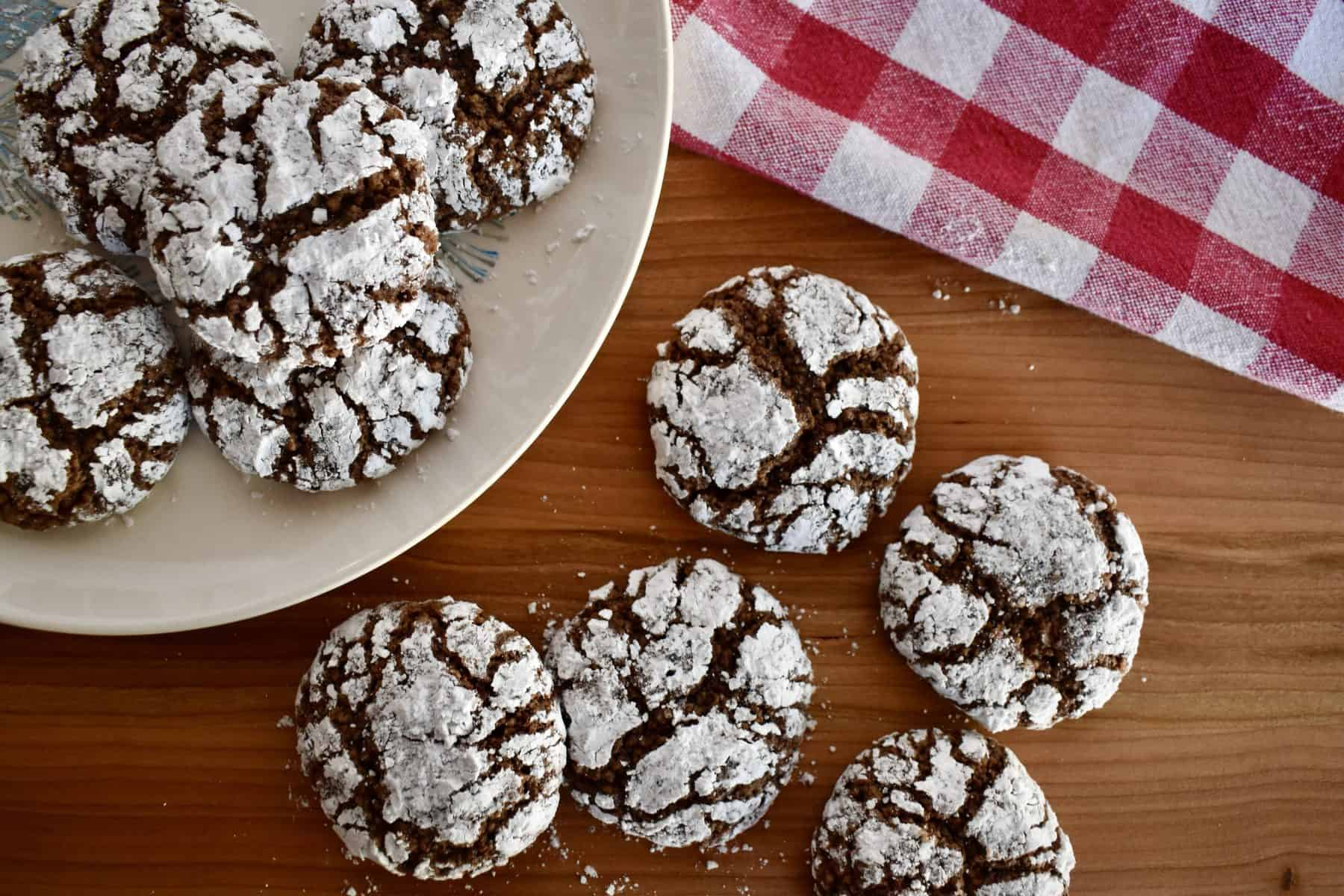 Italian Almond Chocolate Cookies on a wood cutting board with a checkered napkin.