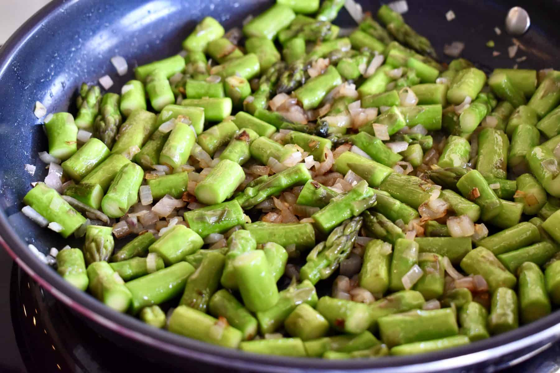 cooked asparagus and shallots in a pan.