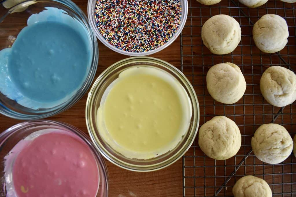 overhead of frosting, sprinkles, and cookies on a wire cooling rack