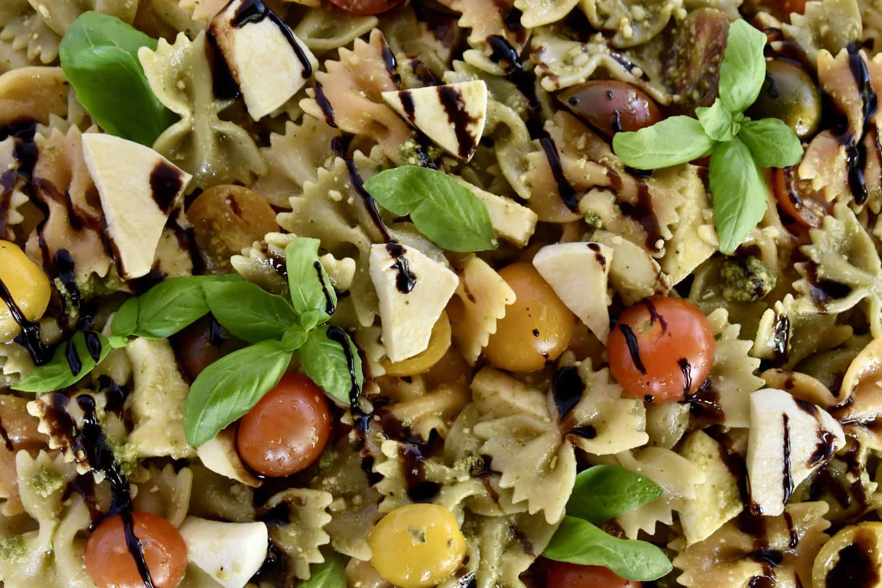 Overhead closeup photo of pesto pasta salad with balsamic drizzle overtop.