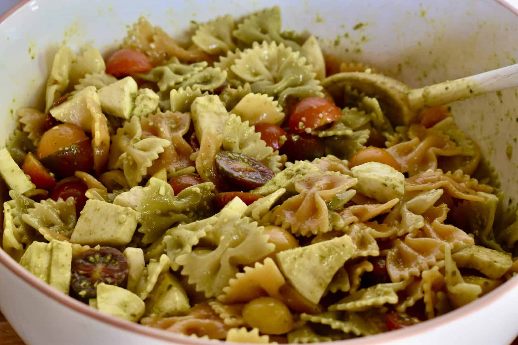 Pesto Pasta Salad tossed together in a large mixing bowl with a wooden spoon.