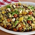 Pesto Pasta Salad in a large white oval platter garnished with basil and balsamic glaze.