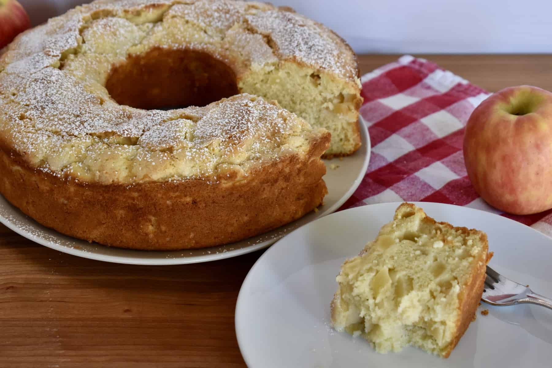 Italian apple cake with a slice of cake on a white plate.