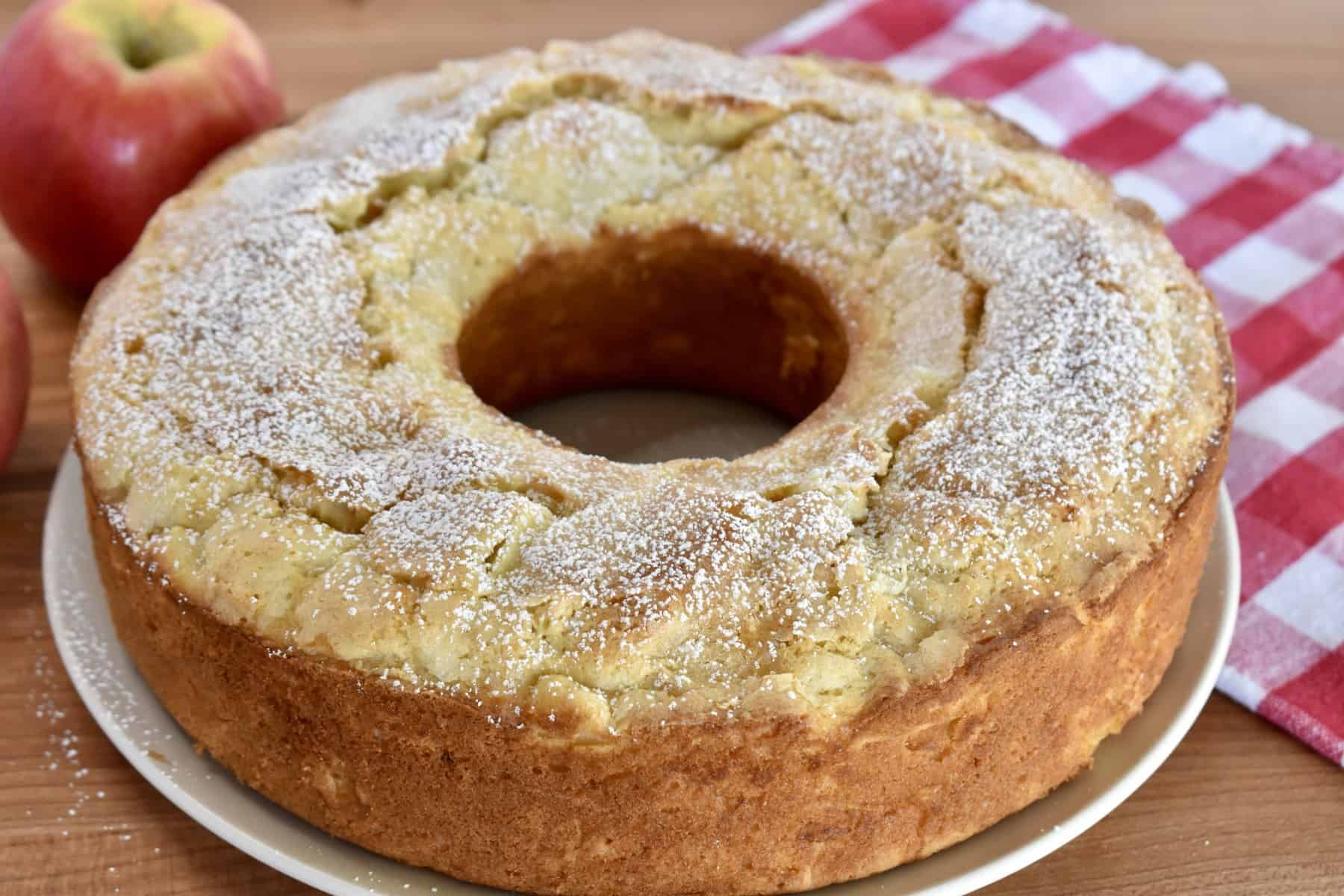 Italian Apple Cake on a wood cutting board with checkered cloth in the background.