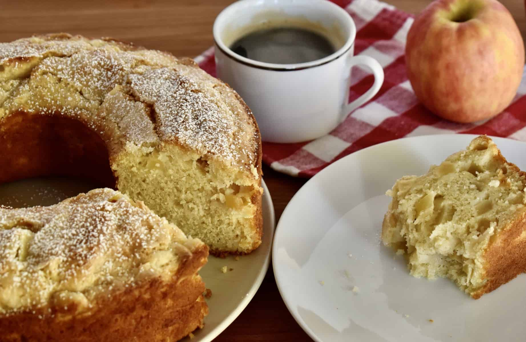 Italian Apple Cut on a counter with a cup of coffee and a plate with slice of cake on it.