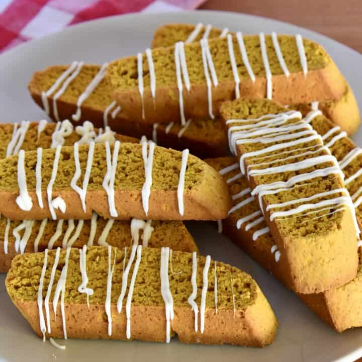 Pumpkin Biscotti with white chocolate drizzle stacked on a plate.