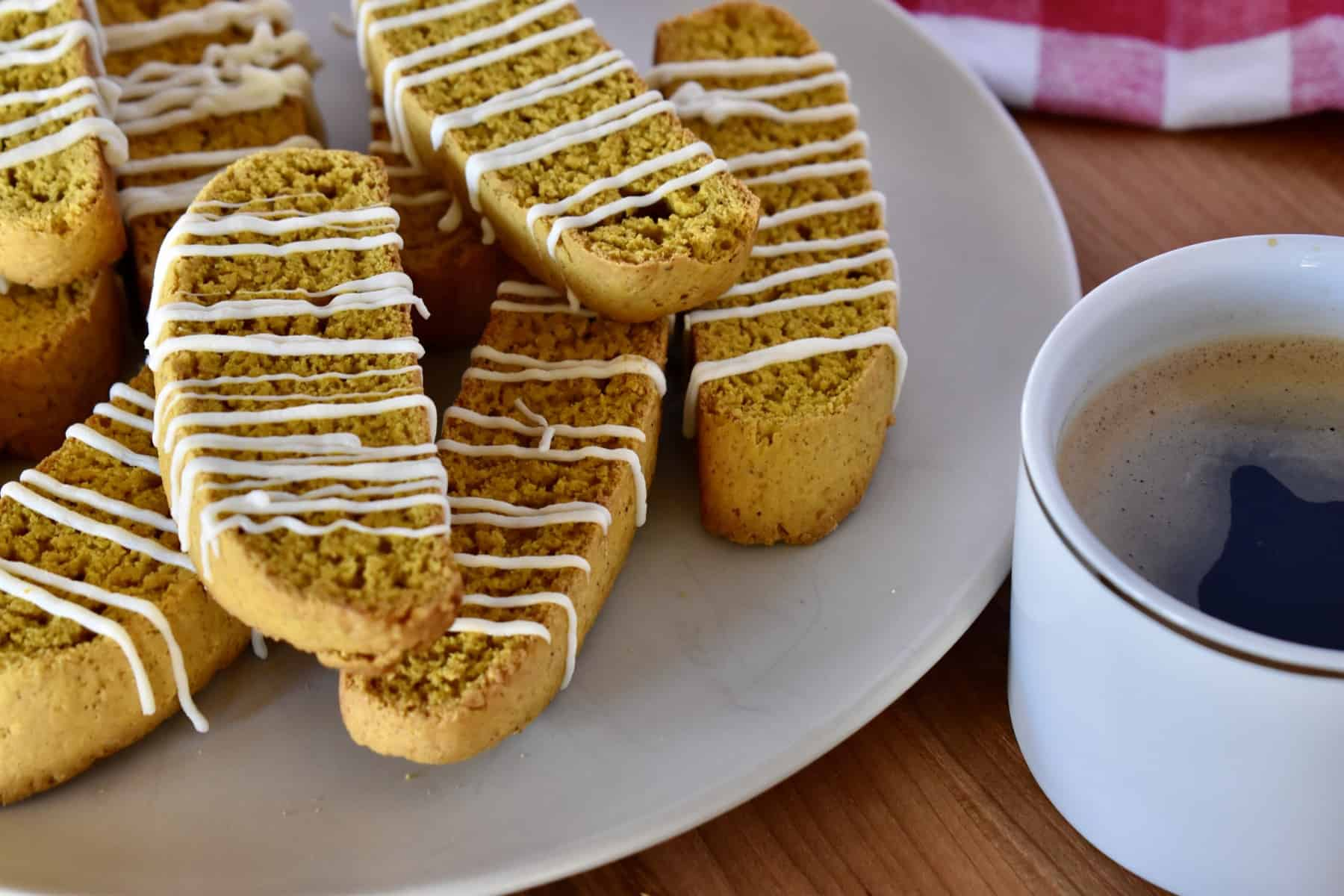 Pumpkin biscotti stacked on a plate with a cup of coffee next to it.