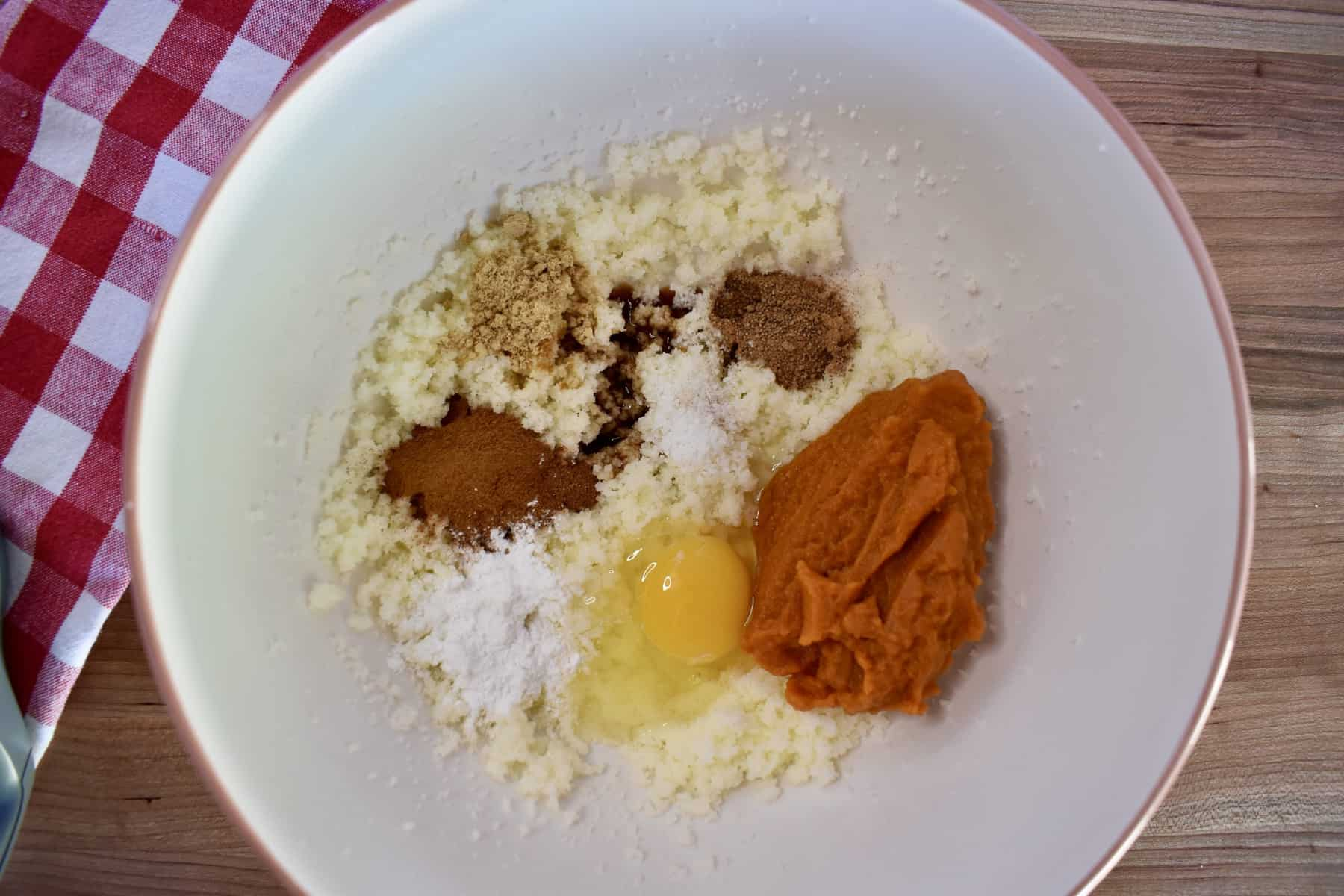 overhead photo of butter, sugar, spices, and puree in a white mixing bowl.