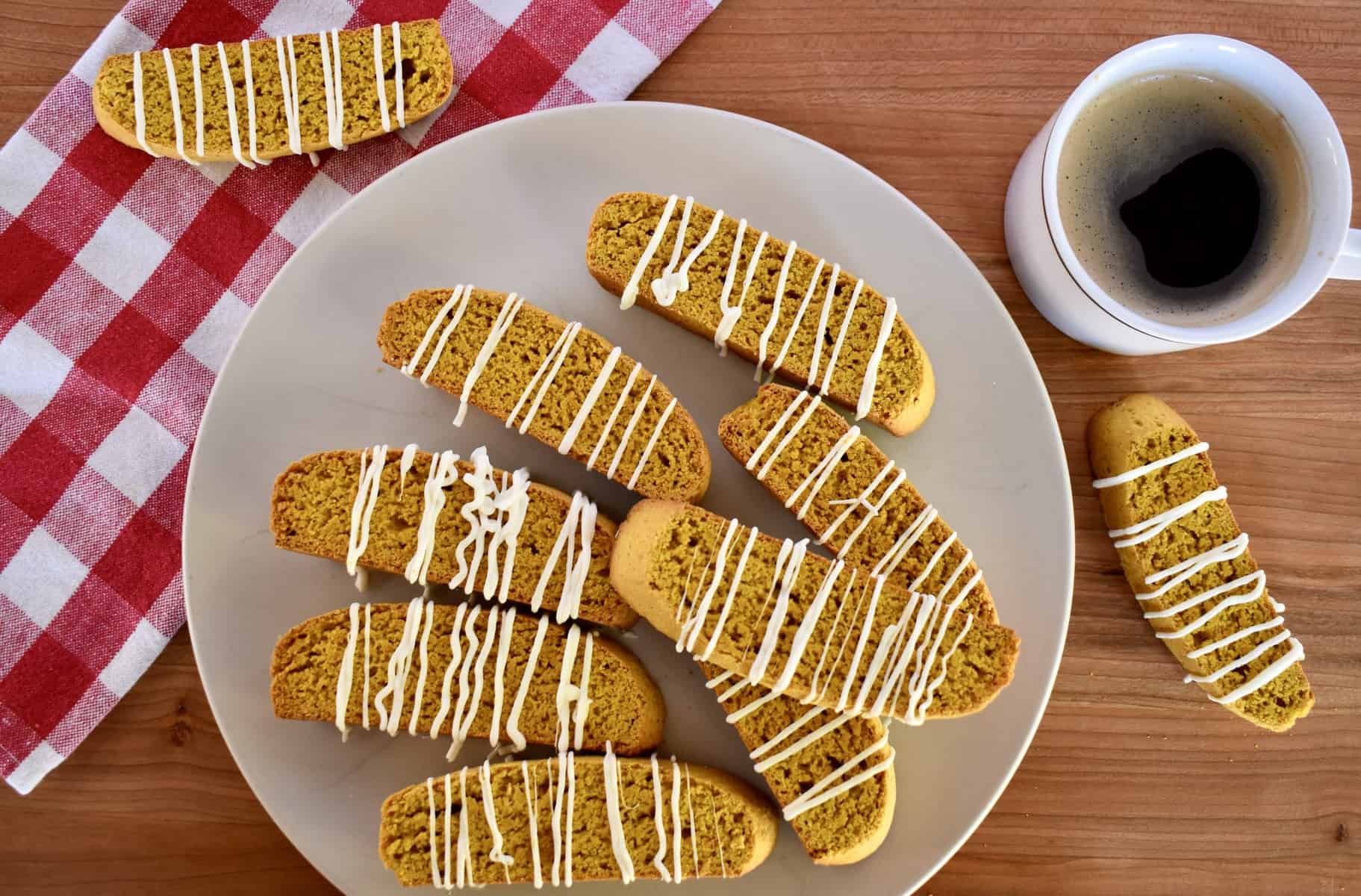 overhead photo of pumpkin biscotti with a cup of black coffee.