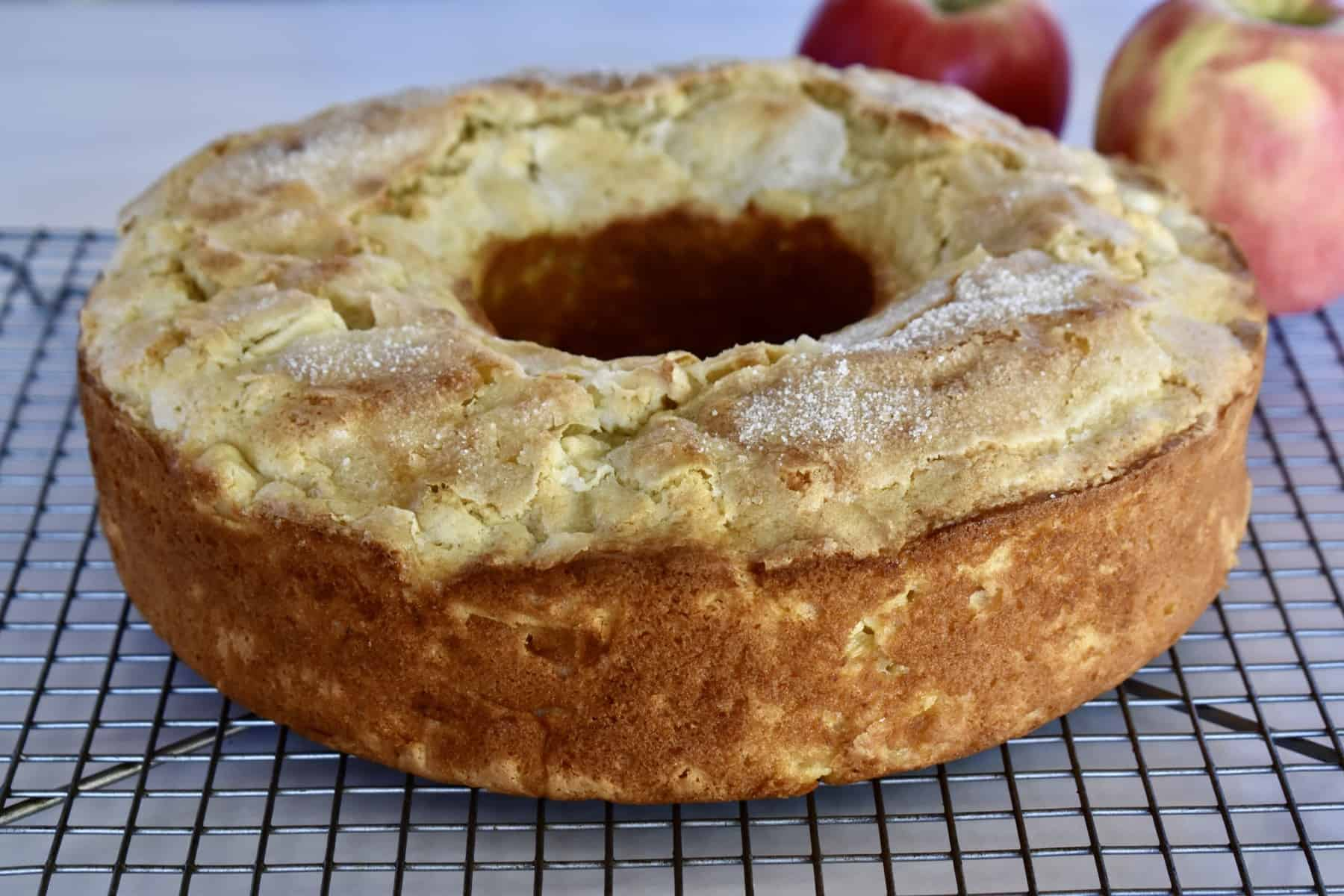 Italian apple cake on a cooling rack with an apple in the background.