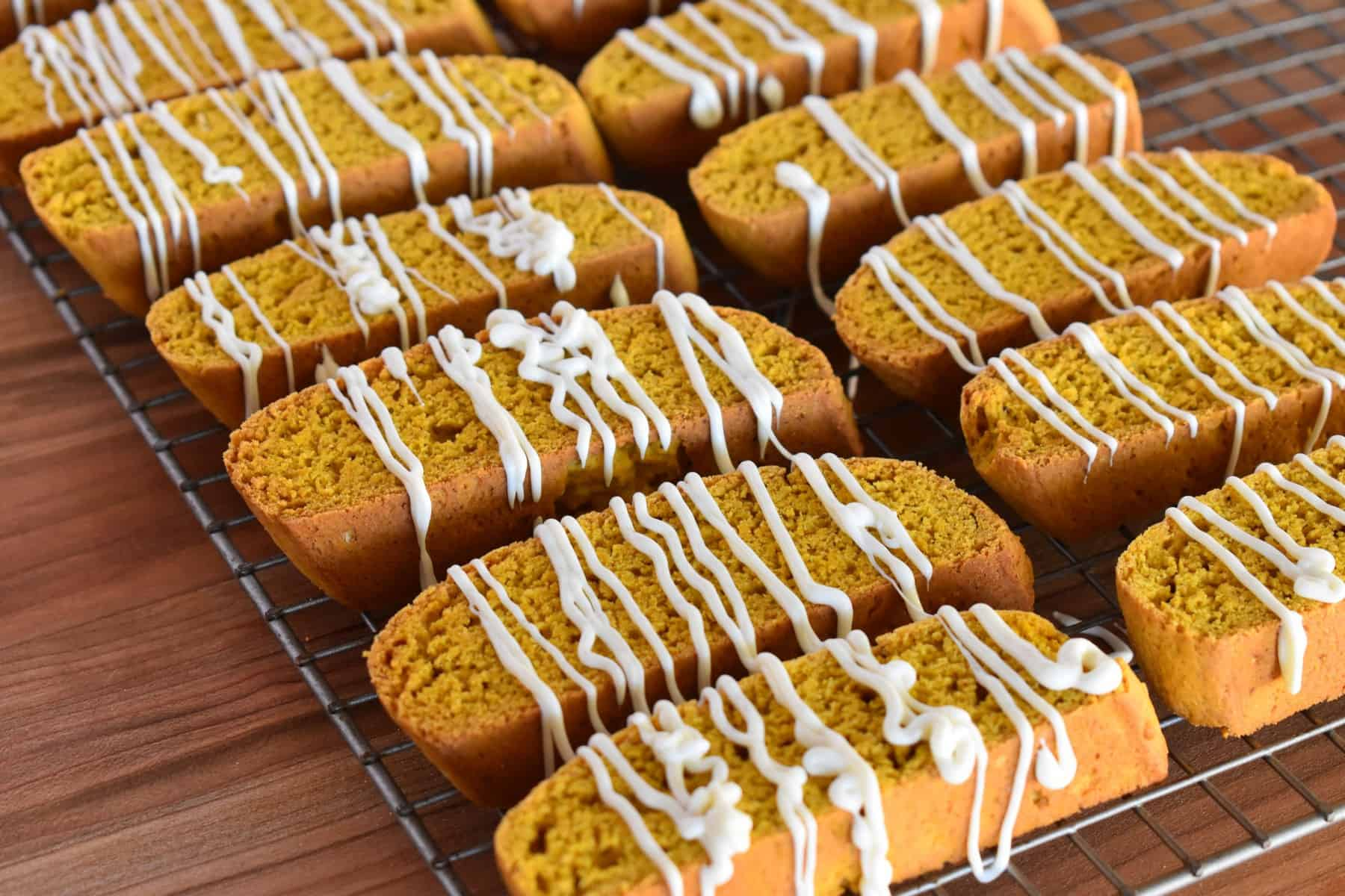 pumpkin biscotti on a wire cooling rack with white chocolate drizzled on them.
