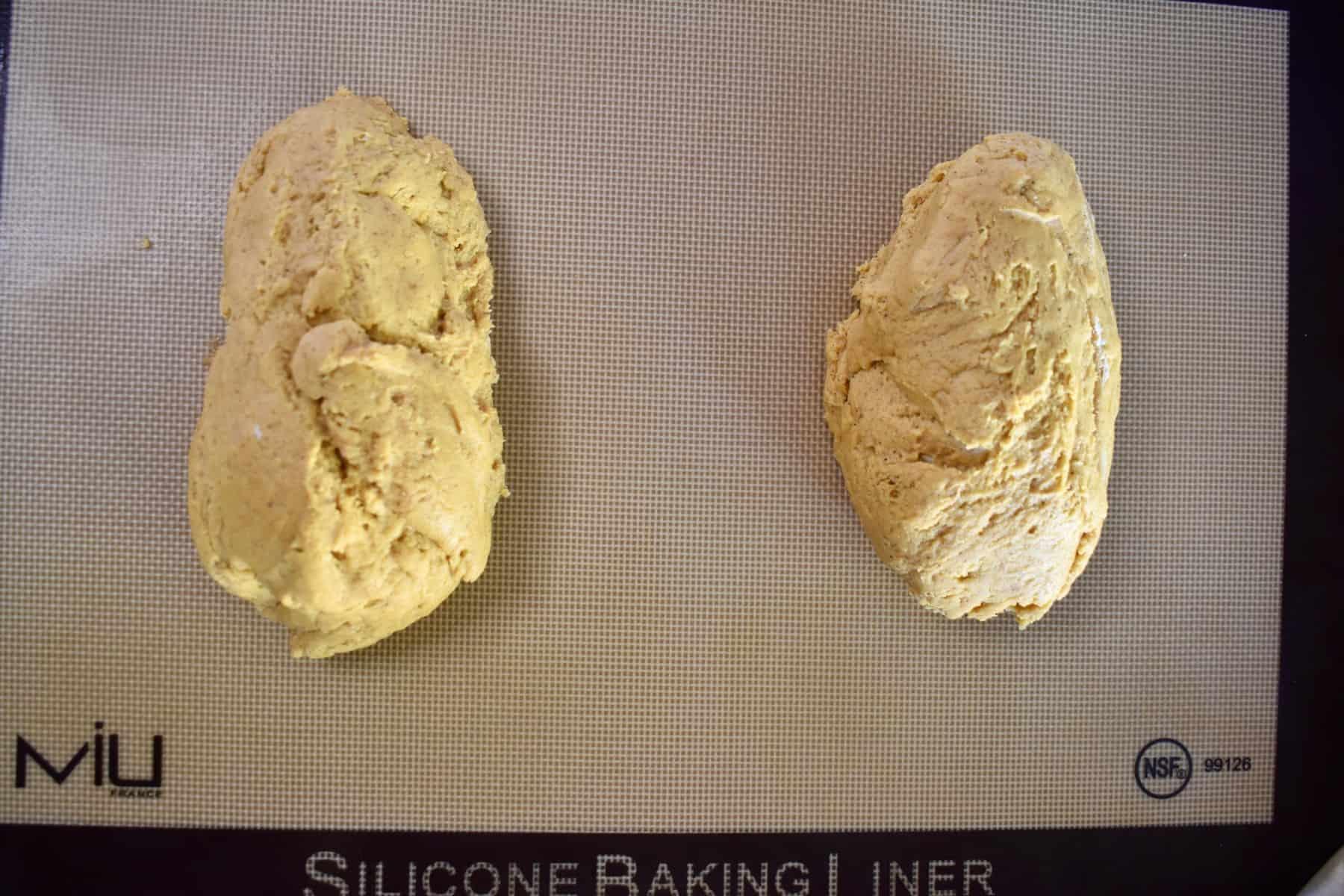 pumpkin biscotti dough in two logs on a baking mat.