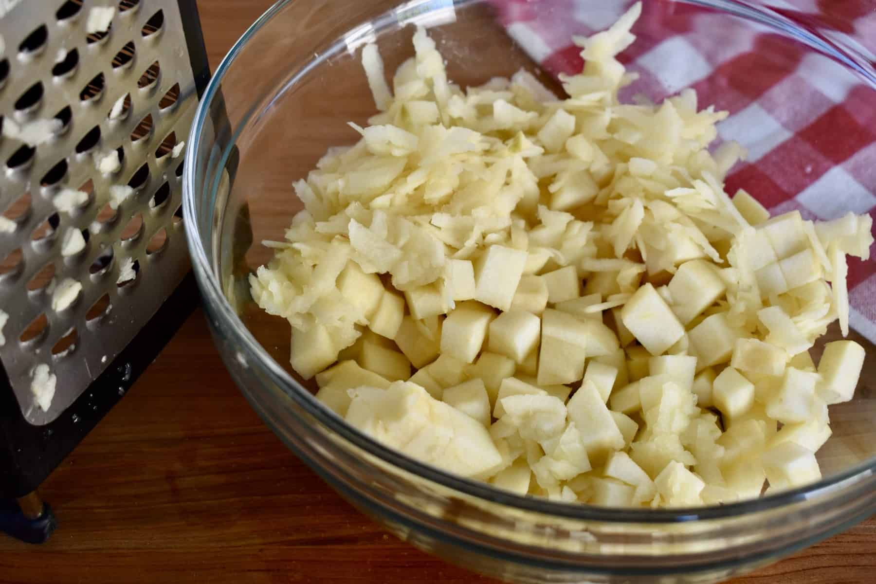 glass bowl with diced and shredded apple in it.
